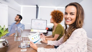 Smiling businesswoman using digital tablet while colleagues discussing in meeting at creative office