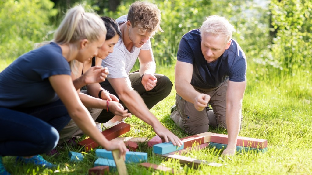 Serious male and female friends planning while stacking building blocks on grassy field in forest