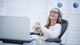 Young woman working in office, laughing
